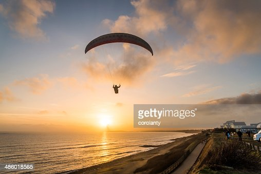 Paraglider flying over beach. : Stock Photo