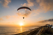 silhouette of a paraglider as he flies above a beach with the sun setting in front of him.