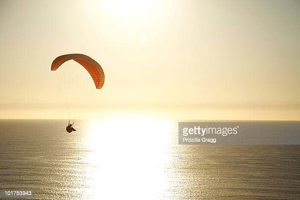 Paraglider rides the wind at sunset over the ocean in California.
