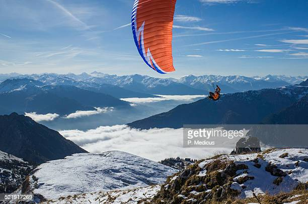 Paraglider soaring above the clouds