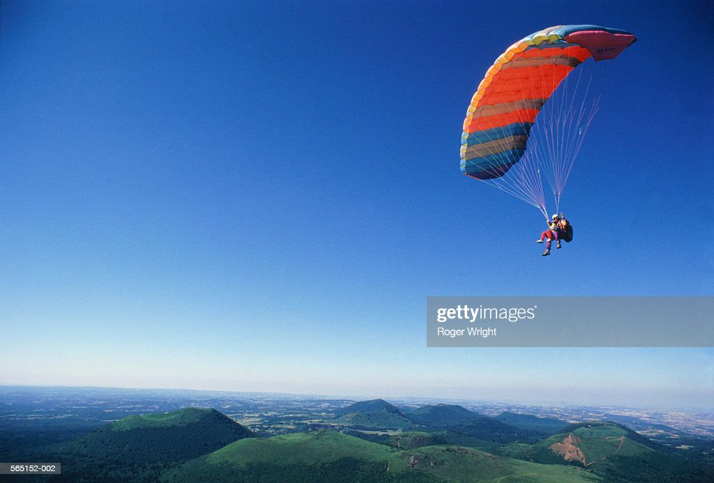 Paraglider with passenger above landscape in clear sky
