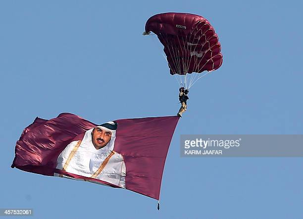 A paraglider with the image of the Emir of Qatar Sheikh Tamim Bin Hamad AlThani glides over the capital during the Gulf emirate's National Day...