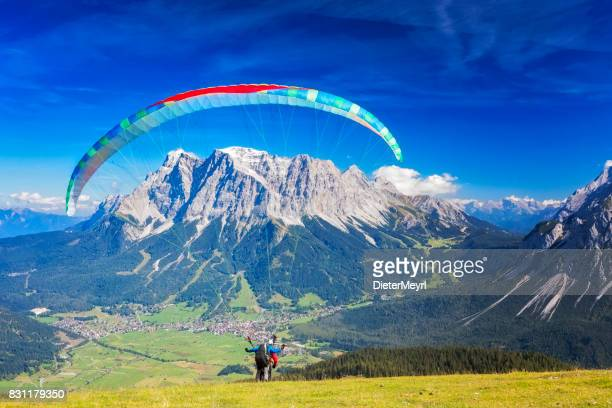 Paragliding in the Alps, Tandem paraglider starting a flight, Mount Zugspitze, Alps