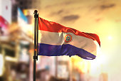 Paraguay Flag Against City Blurred Background At Sunrise Backlight