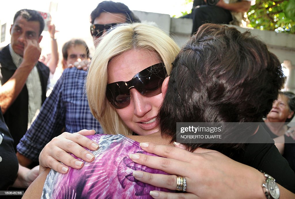 Paraguayan deputy Fabiola Oviedo (L), daughter of former general and UNACE party presidential candidate Lino Oviedo --who died along with his bodyguard Denis Galeano and pilot Ramon Picco Delmas in a helicopter crash on February 2-- is comforted by her father's supporters upon her arrival at the morgue in Asuncion on February 4, 2013. Oviedo, 69, the controversial presidential candidate who helped topple Paraguayan dictator Alfredo Stroessner in 1989, died when the aircraft crashed en route to Asuncion while returning from a campaign rally in northern Paraguay, prompting claims of foul play. AFP PHOTO/Norberto DUARTE
