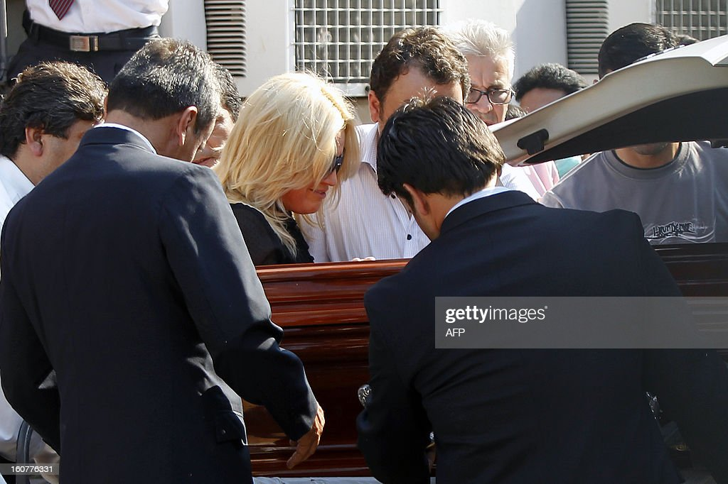 Paraguayan deputy Fabiola Oviedo (2nd L), daughter of former general and UNACE party presidential candidate Lino Oviedo --who died along with his bodyguard Denis Galeano and pilot Ramon Picco Delmas in a helicopter crash on February 2-- mourns next to her father's coffin at the morgue in Asuncion on February 5, 2013. Oviedo, 69, the controversial presidential candidate who helped topple Paraguayan dictator Alfredo Stroessner in 1989, died when the aircraft crashed en route to Asuncion while returning from a campaign rally in northern Paraguay, prompting claims of foul play. AFP PHOTO