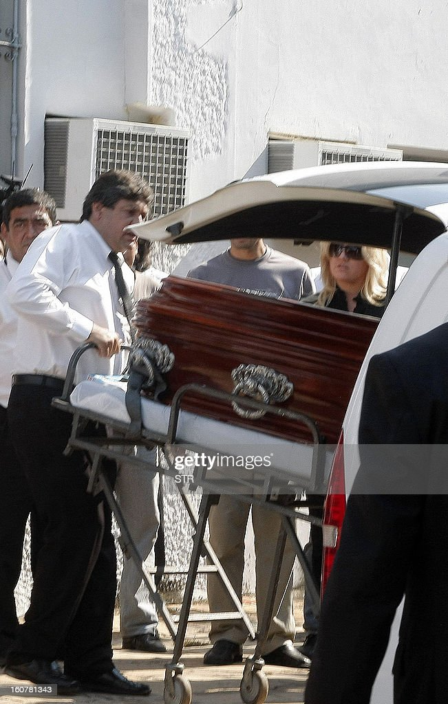 Paraguayan deputy Fabiola Oviedo (R), daughter of former general and UNACE party presidential candidate Lino Oviedo --who died along with his bodyguard Denis Galeano and pilot Ramon Picco Delmas in a helicopter crash on February 2-- mourns next to her father's coffin at the morgue in Asuncion on February 5, 2013. Oviedo, 69, the controversial presidential candidate who helped topple Paraguayan dictator Alfredo Stroessner in 1989, died when the aircraft crashed en route to Asuncion while returning from a campaign rally in northern Paraguay, prompting claims of foul play. AFP PHOTO / STR