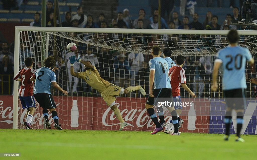 Paraguayan goalkeeper Diego Barreto (C) dives for the ball during their FIFA World Cup Brazil 2014 South American qualifying football match against Uruguay in Montevideo, Uruguay on March 22, 2013. AFP PHOTO / PABLO PORCIUNCULA