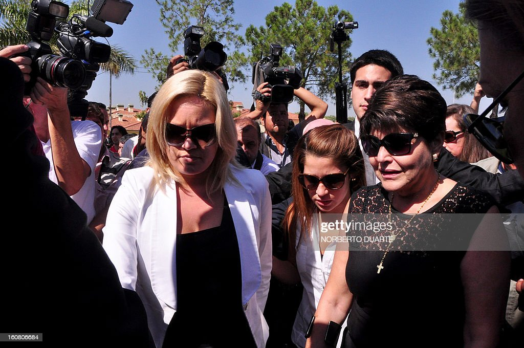 Paraguayan national deputy Faviola Oviedo (L) and Raquel Marin de Oviedo, daughter and wife respectively, of former general and UNACE party presidential candidate Lino Oviedo - who died along with his bodyguard Denis Galeano and pilot Ramon Picco Delmas in a helicopter crash on February 2 - attend his funeral in Asuncion on February 6, 2013. Oviedo, 69, the controversial presidential candidate who helped topple Paraguayan dictator Alfredo Stroessner in 1989, died when the aircraft crashed en route to Asuncion while returning from a campaign rally in northern Paraguay, prompting claims of foul play. AFP PHOTO /Norberto Duarte