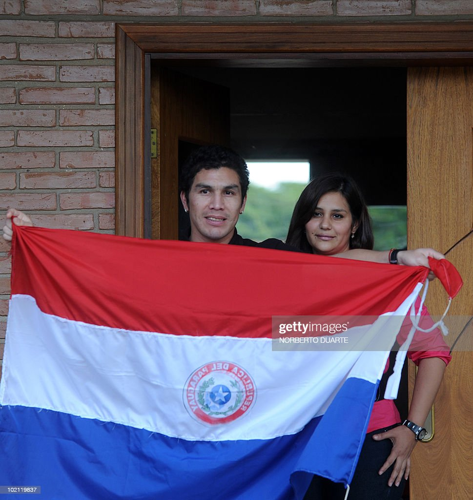 Paraguayan national football team player Salvador Cabanas shows a Paragayan national flag next to his wife Maria Alonso at their home in Asuncion on June 15, 2010. Cabanas was seriously injured when he was shot past January 25 in a bar in Mexico City. AFP PHOTO / Norberto Duarte