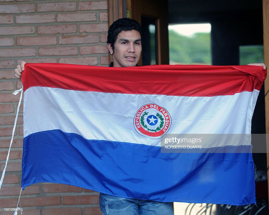 Paraguayan national football team player Salvador Cabanas shows a Paragayan national flag at his home in Asuncion on June 15, 2010. Cabanas was seriously injured when he was shot past January 25 in a bar in Mexico City. AFP PHOTO / Norberto Duarte