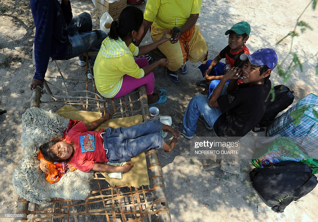 Paraguayan natives from the Comunidad Esperanza, in Chaco, 240 km north of Asuncion, wait for supplies from the UN World Food Programme (WFP) on October 2, 2012. About 1,800,000 kg of food were distributed among 59 communities --some 50,000 people-- in three localities of Chaco, stricken earlier this year by unusual floods.
