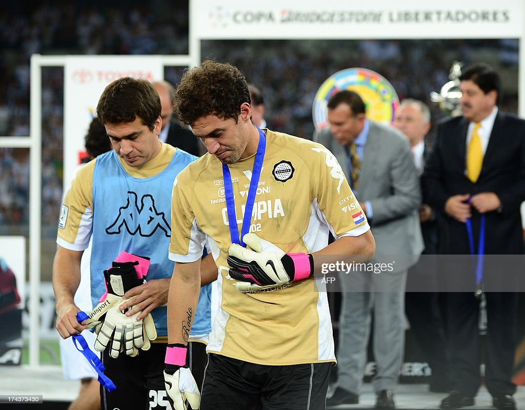 Paraguayan Olimpia's goalkeeper Martin Silva leaves with the silver medal after the Libertadores Cup second leg final football match against Brazilian Atletico Mineiro the Mineirao stadium in Belo Horizonte, Brazil on July 24, 2013. Atletico Mineiro won by 4-3 after a penalty shoot-out. AFP PHOTO / DOUGLAS MAGNO