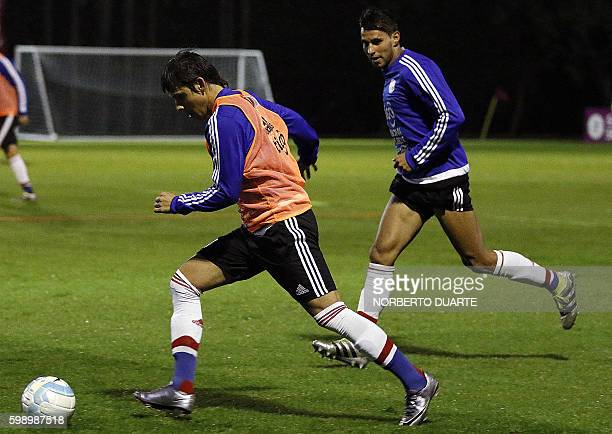 Paraguayan players Oscar Romero and Roque Santa Cruz take part in a training session at the Albiroga training center in Ypane Paraguay on September 3...