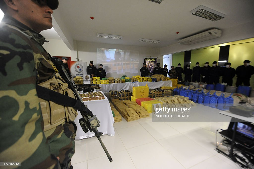 Paraguayan policemen from a special unit custody drugs seized during the Aguila Negra (Black Eagle) operation carried out in the EEP guerrillas-controlled area, in Asuncion on August 23, 2013. 1726 kg of cocaine and 1726 kg of marijuana worth USD 100 million were seized, General Prosecutor Javier Diaz Veron said. AFP PHOTO/NORBERTO Duarte