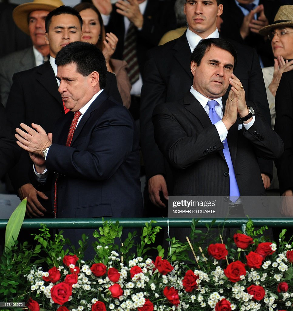 Paraguayan President Federico Franco (R) and President-elect Horacio Cartes applaud during the opening of the country's biggest annual trade fair, in Mariano Roque Alonso, on July 13, 2013. On Friday the Mercosur trade bloc meeting in Montevideo agreed to reinstate Paraguay's membership once rightwing tycoon Horacio Cartes, elected president in April, takes office on August 15. Cartes however appeared to reject the offer saying that Venezuela's admission to the group did not follow the proper legal procedure. Argentina, Brazil and Uruguay suspended Paraguay from Mercosur after Paraguay's Congress impeached leftist president Fernando Lugo and removed from office in June 2012. With Paraguay gone, Argentina, Brazil and Uruguay admitted leftist Venezuela as a Mercosur member. AFP PHOTO / Norberto DUARTE