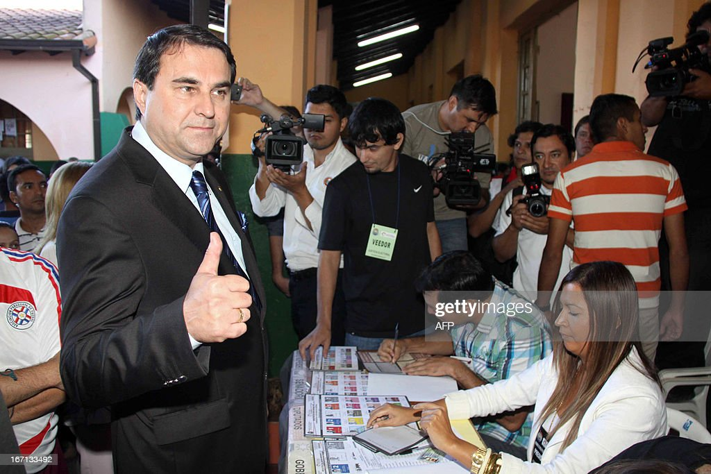 Paraguayan President Federico Franco (L) gestures at a polling station in Asuncion on April 21, 2013. Voters in Paraguay cast ballots Sunday to choose a new leader and try to turn the page on a political crisis that saw the impeachment of leftist president Fernando Lugo ten months ago. AFP PHOTO/Jorge Romero