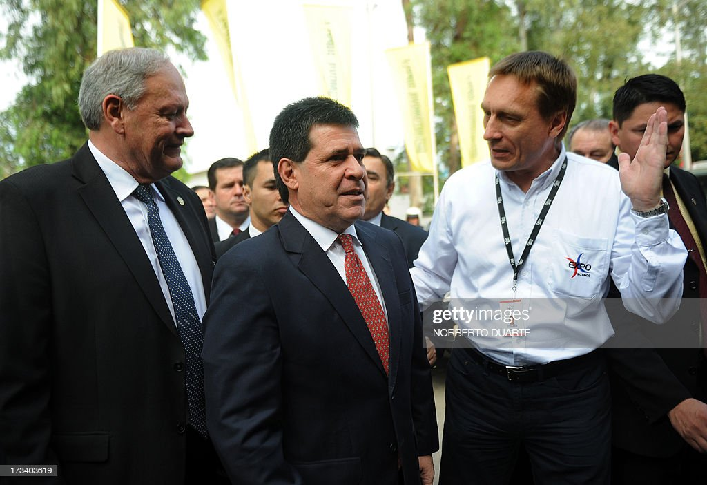 Paraguayan President-elect Horacio Cartes (C) is welcomed by businessmen as he arrives for the opening of the country's biggest annual trade fair, in Mariano Roque Alonso, on July 13, 2013. On Friday the Mercosur trade bloc meeting in Montevideo agreed to reinstate Paraguay's membership once rightwing tycoon Horacio Cartes, elected president in April, takes office on August 15. Cartes however appeared to reject the offer saying that Venezuela's admission to the group did not follow the proper legal procedure. Argentina, Brazil and Uruguay suspended Paraguay from Mercosur after Paraguay's Congress impeached leftist president Fernando Lugo and removed from office in June 2012. With Paraguay gone, Argentina, Brazil and Uruguay admitted leftist Venezuela as a Mercosur member. AFP PHOTO / Norberto DUARTE