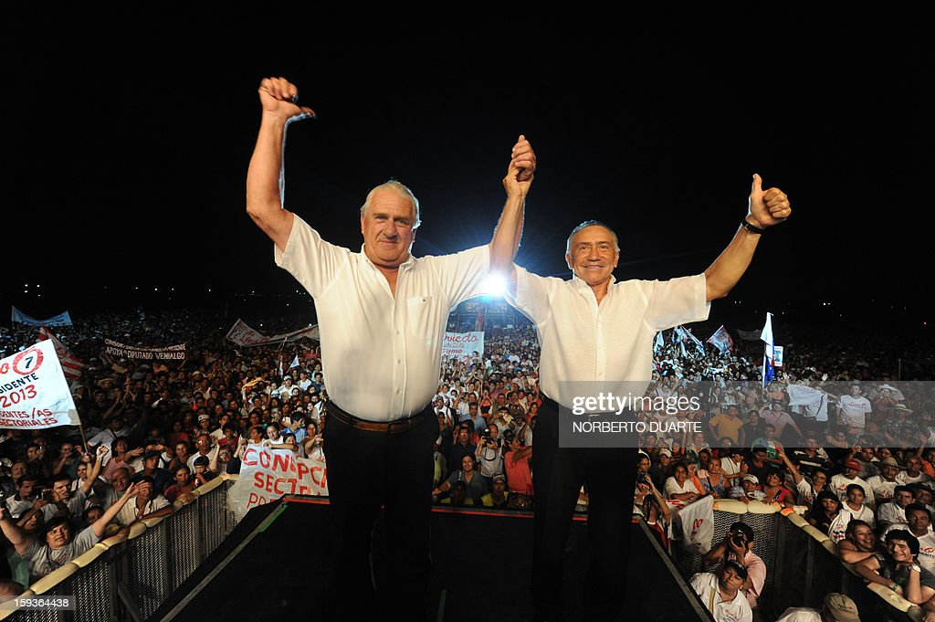 Paraguayan presidential candidate for the National Union of Ethical Citizens (UNACE) party, Lino Oviedo (R), and Vice-Presidential candidate, Alberto Johanssen, are greeted by supporters during a rally for the initiation of his political campaign in Luque, Paraguay on, January 12 , 2013. Paraguay will hold presidential elections on April 21, 2013. AFP PHOTO/Norberto Duarte