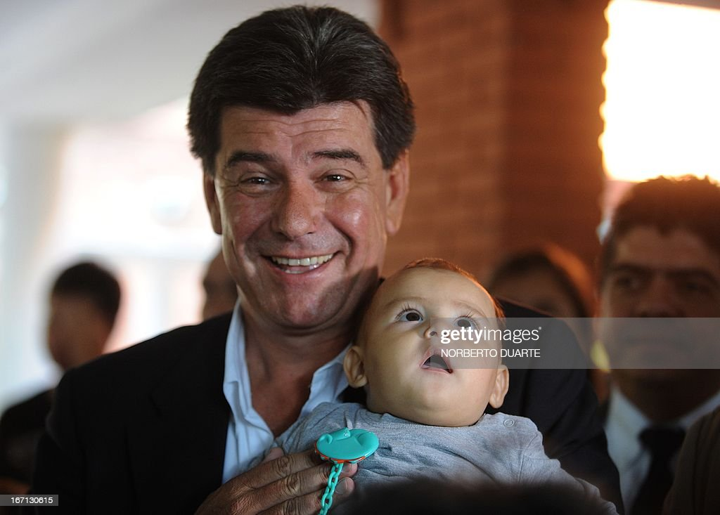 Paraguayan presidential candidate of the ruling Liberal Party Efrain Alegre smiles while holding a baby at a polling station in Asuncion on April 21, 2013. Voters in Paraguay cast ballots Sunday to choose a new leader and try to turn the page on a political crisis that saw the impeachment of leftist president Fernando Lugo ten months ago. AFP PHOTO/Norberto Duarte