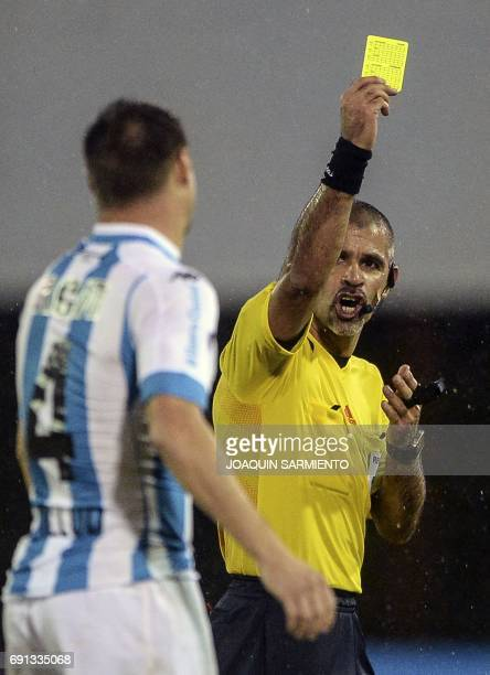 Paraguayan referee Eber Aquino shows a yellow card to Argentina´s Racing player Ivan Pillud during their 2017 Copa Sudamericana football match...