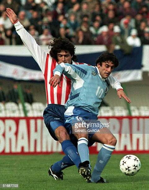 Paraguayan Roberto Acuna tries to take the ball from Enzo Francescoli of Uruguayauthor of his team's first goal 09 July during the Copa America's...