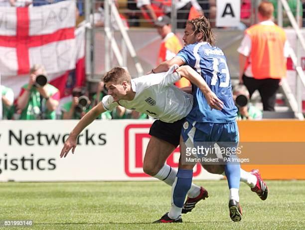 Paraguay's Carlos Paredes challenges England's Steven Gerrard