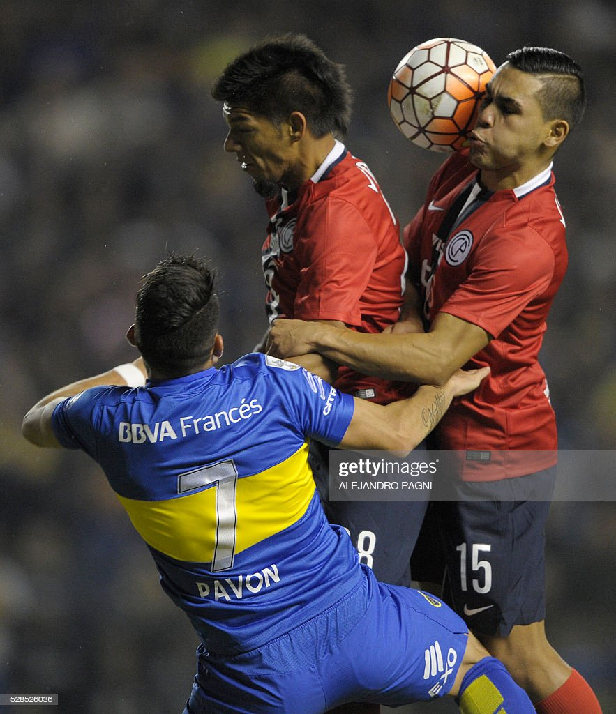 Paraguay's Cerro Porteno midfielder Jorge Rojas (R) heads the ball next his teammate midfielder Marcos Riveros and Argentina's Boca Juniors forward Cristian Pavon (L) during their Copa Libertadores 2016 round before the quarterfinals second leg football match at La Bombonera stadium in Buenos Aires, Argentina, on May 5, 2016. / AFP / ALEJANDRO