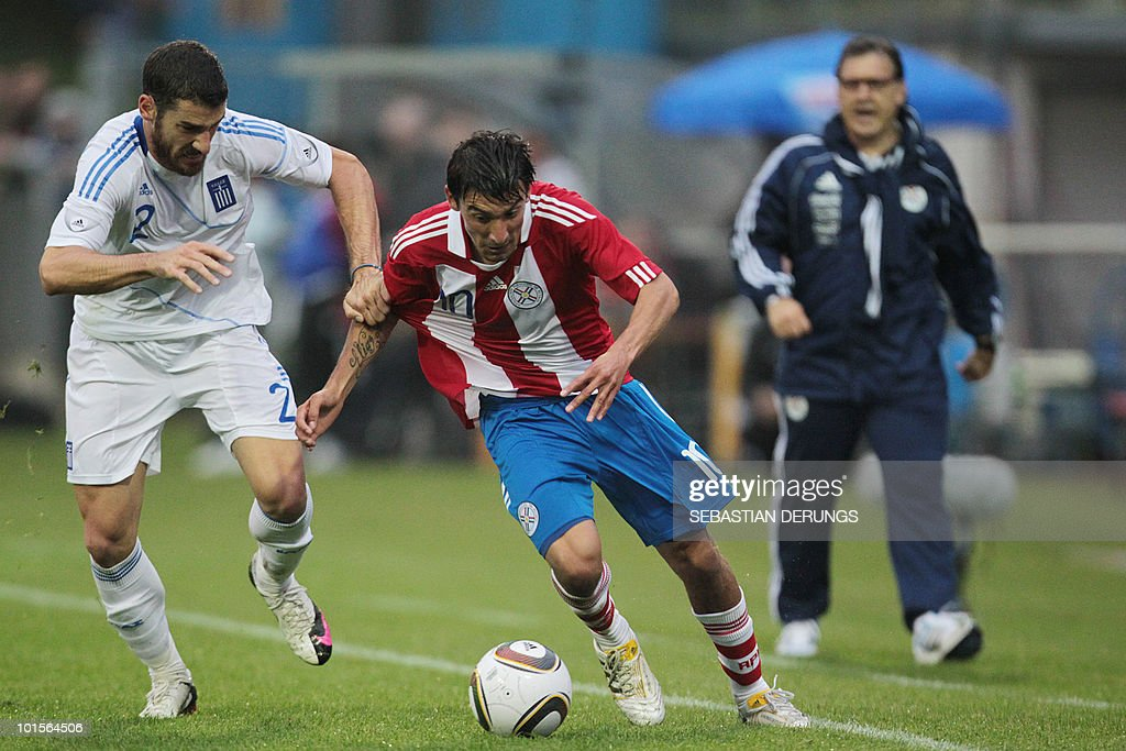 Paraguay's coach Gerardo Martino watches Paraguay's Edgar Benitez fighting for the ball with Greece's Georgios Seitaridis during a friendly football...