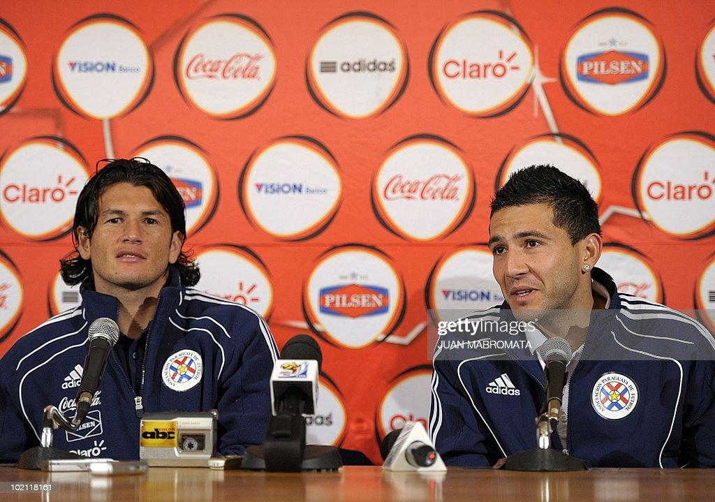 Paraguay's defender Antolin Alcaraz (R) talks to journalist next to teammate forward Nelson Haedo during a press conference at Michaelhouse School in Balgowan on June 15, 2010, a day after their 0-0 tie with Italy in the 2010 World Cup in South Africa.