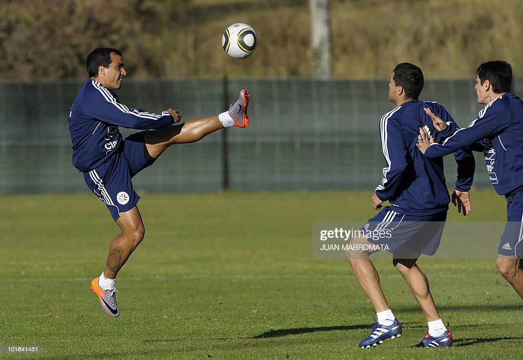 Paraguay's defender Claudio Morel Rodriguez (L) kicks the ball as teammates Antolin Alcaraz (C) and Denis Caniza look on during a training session at the Michaelhouse school in Balgowan on June 5, 2010. Pararguay will face Italy in their opening match of the 2010 World Cup South Africa in Cape Town on June 14.