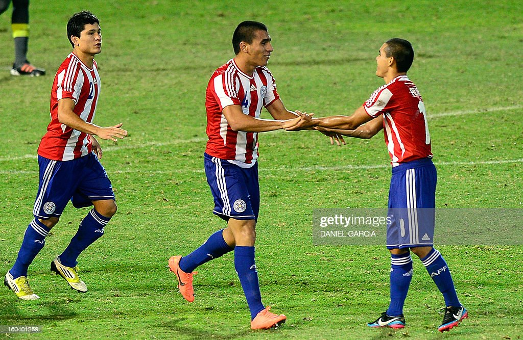 Paraguay's defender Junior Alonso (C) celebrates with teammate midfielder Angel Cardozo (R) after he scored against Uruguay during their South American U-20 final round football match at Malvinas A...