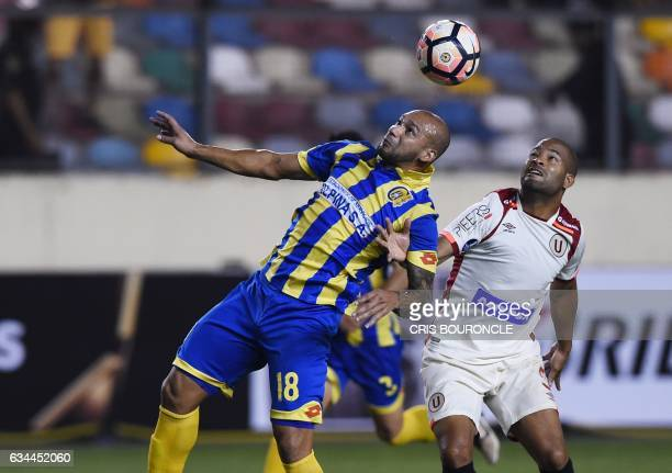 Paraguays Deportivo Capiata player Dioniso Perez Mambreani vies for the ball with Perus Universitario player John Galliquio during their firstround...