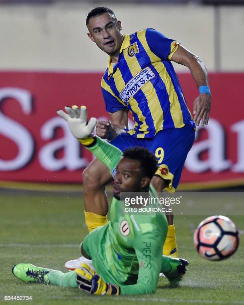 Paraguays Deportivo Capiata player Roberto Gamarra shoots to score over Perus Universitario goalie Carlos Caceda in their firstround Copa...