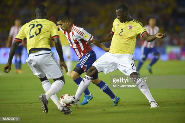 Paraguay's Derlis Gonzalez struggles for the ball with Colombia's Davinson Sanchez and Colombia's Cristian Zapata during their 2018 World Cup...