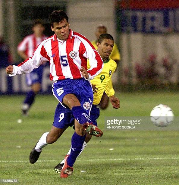 Paraguay's forward Celso Ayala kicks the ball past the defense of Brazil's Djalminha 18 July during their JapanKorea 2002 World Cup qualification...