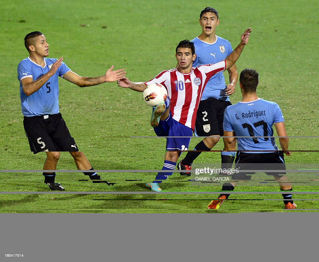 Paraguay's forward Derlis Gonzalez vies for the ball with Uruguay's midfielder Jim Varela, defender Emiliano Velazquez and defender Gianni Danielle Rodriguez during their South American U-20 final round football match at Malvinas Argentinas stadium in Mendoza, Argentina, on January 30, 2013. Four teams will qualify for the FIFA U-20 World Cup Turkey 2013. AFP PHOTO / DANIEL GARCIA