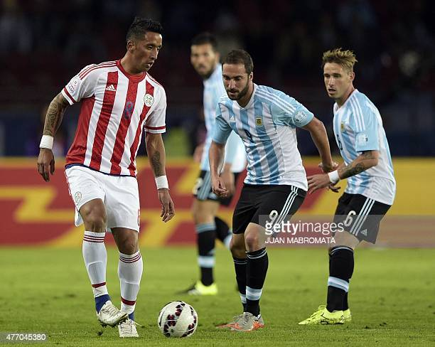 Paraguay's forward Lucas Barrios and Argentina's forward Gonzalo Higuain vie for the ball during their 2015 Copa America football championship match...