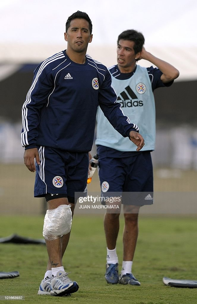 Paraguay's forward Lucas Barrios (L) walks with an ice bag on his knee as he leaves the field with midfielder Victor Caceres after a training session at Harry Gwala stadium in Pietermaritzburg on June 6, 2010 ahead of the 2010 World Cup in South Africa.