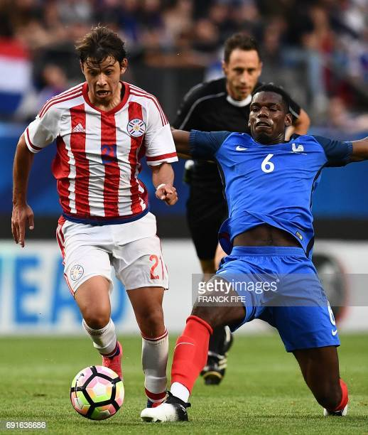 Paraguay's forward Oscar Romero vies with France's midfielder Paul Pogba during a friendly football match between France and Paraguay on June 2 at...