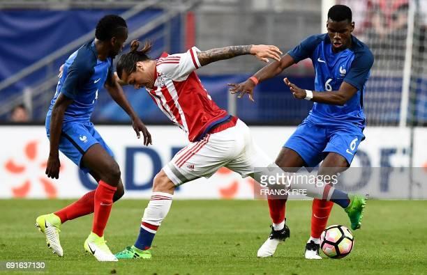 Paraguay's forward Oscar Romero vies with France's midfielder Paul Pogba and France's midfielder Blaise Matuidi during the friendly football match...