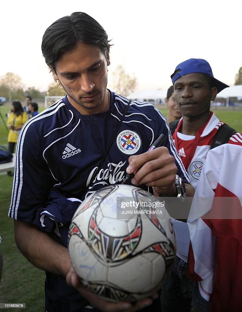 Paraguay's forward Roque Santa Cruz signs an autograph on a ball for a fan after a training session at Harry Gwala stadium in Pietermaritzburg on June 6, 2010 ahead of the 2010 World Cup in South Africa.