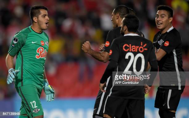 Paraguay's Libertad goalkeeper Carlos Servin celebrates with teammates after stopping Colombia's Santa Fe Anderson Plata shot during their Copa...