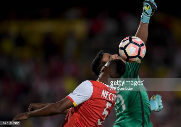 Paraguay's Libertad goalkeeper Carlos Servin tries to stop a header by Colombia's Santa Fe Juan Valencia during their Sudamericana football match at...