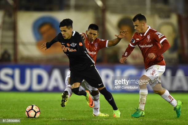 Paraguay's Libertad midfielder Jesus Manuel Medina Maldonado vies for the ball with Argentina's Huracan midfielder Leandro Emanuel Cuomo during their...