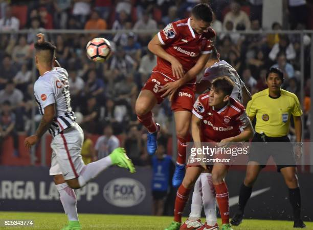 Paraguay's Libertad player Alan Benitez vies for the ball with Argentina's Huracan Fernando Cosciuc and Lucas Villalba during their Copa Sudamericana...