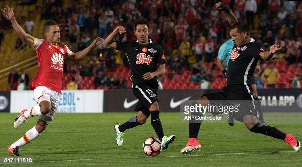 Paraguay's Libertad player Angel Cardozo vies for the ball with Colombia's Santa Fe player John Pajoy during their 2017 Copa Sudamericana football...