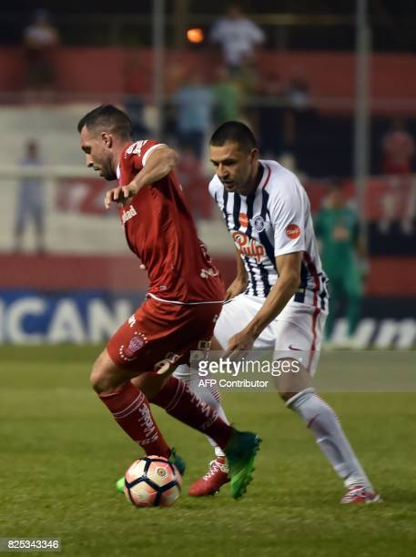 Paraguay's Libertad player Danilo Santacruz vies for the ball with Argentina's Huracan Mariano Gonzalez during their Copa Sudamericana 2017 second...