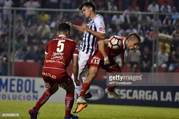 Paraguay's Libertad player Jesus Medina vies for the ball with Argentina's Huracan Cristian Chimino and Fernando Cosciuc during their Copa...