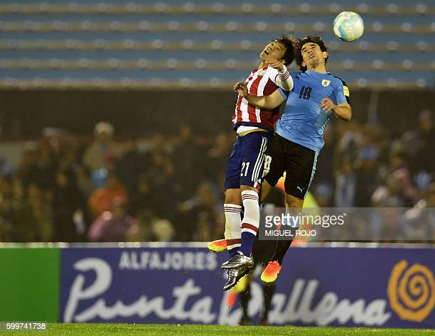 Paraguay's midfielder Oscar Romero and Uruguay's Mathias Corujo jump for a header during their Russia 2018 World Cup football qualifier match in...